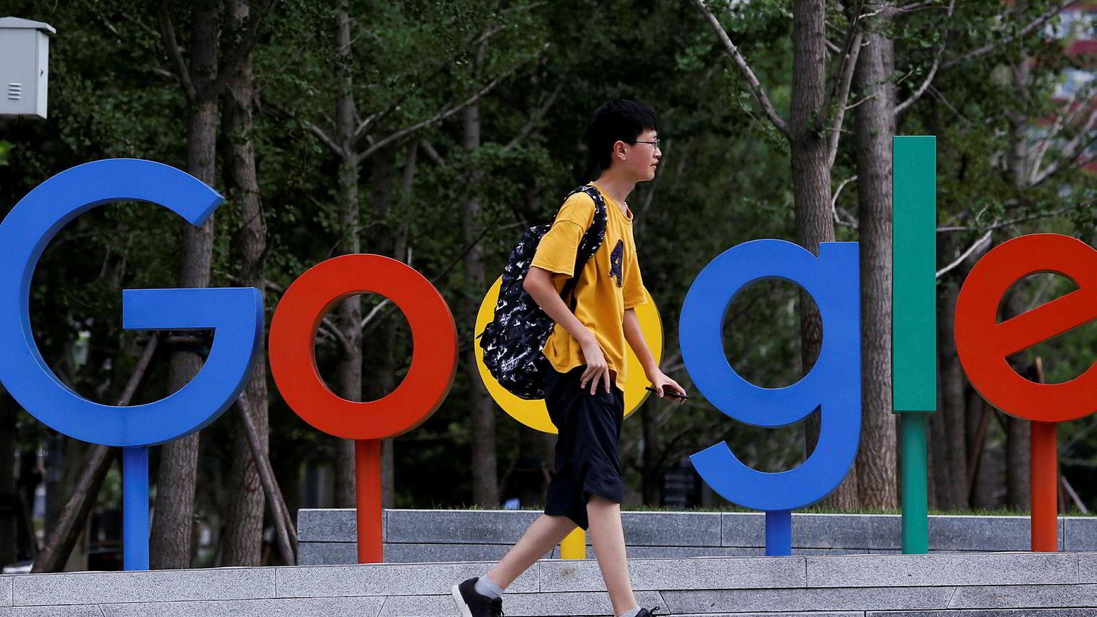 En mann går forbi Googles kontorer i Beijing. Nå protesterer ansatte i Google mot en sensurtilpasset versjon av søkemotoren.