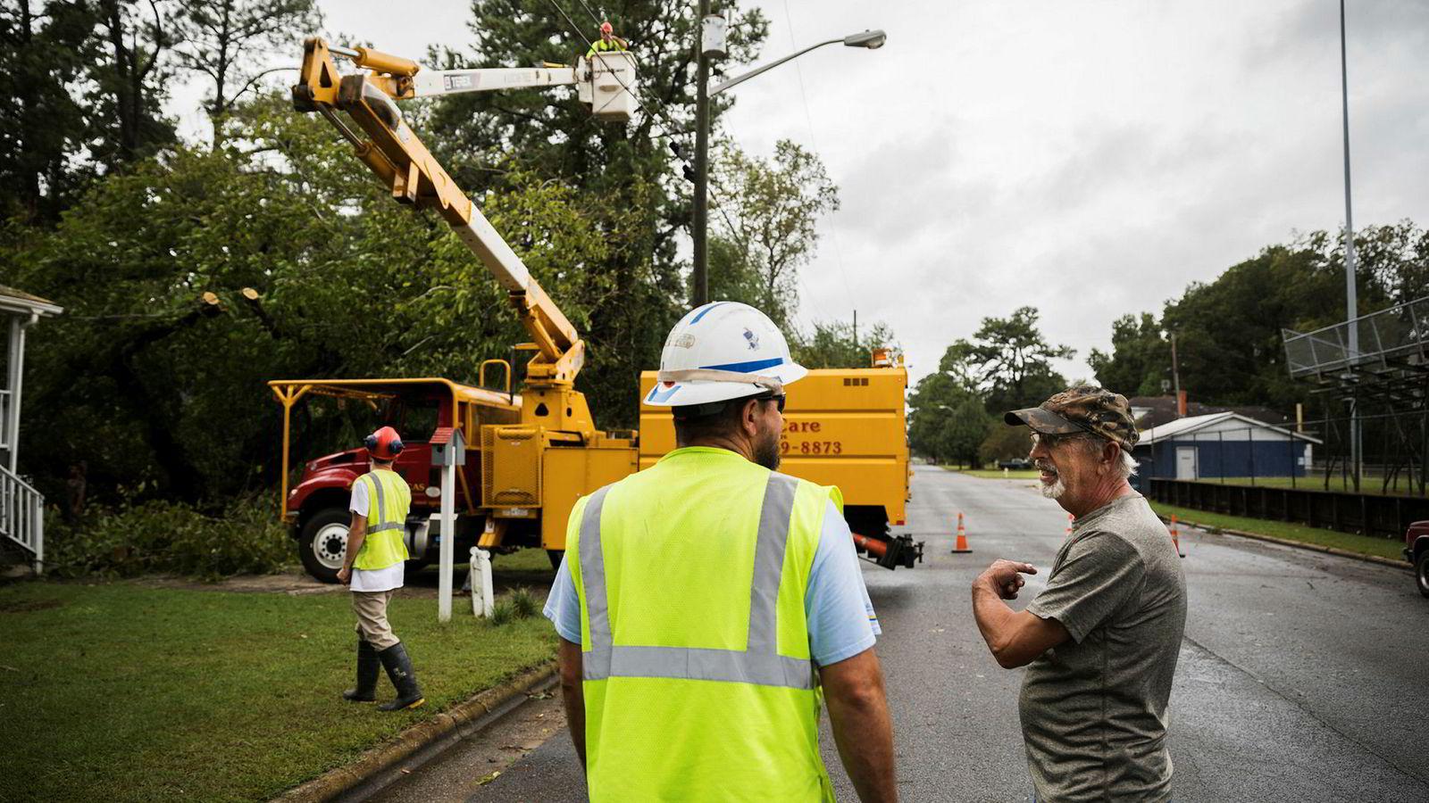 Kenny McConville beredskapskoordinator i kommunen (til venstre), ser til at et tre blir fjernet fra strømlinjene til huset til Dennis Lilley. Byen Washington i Nord Carolina ble kraftig oversvømmet, men vannet har trukket seg mye tilbake.