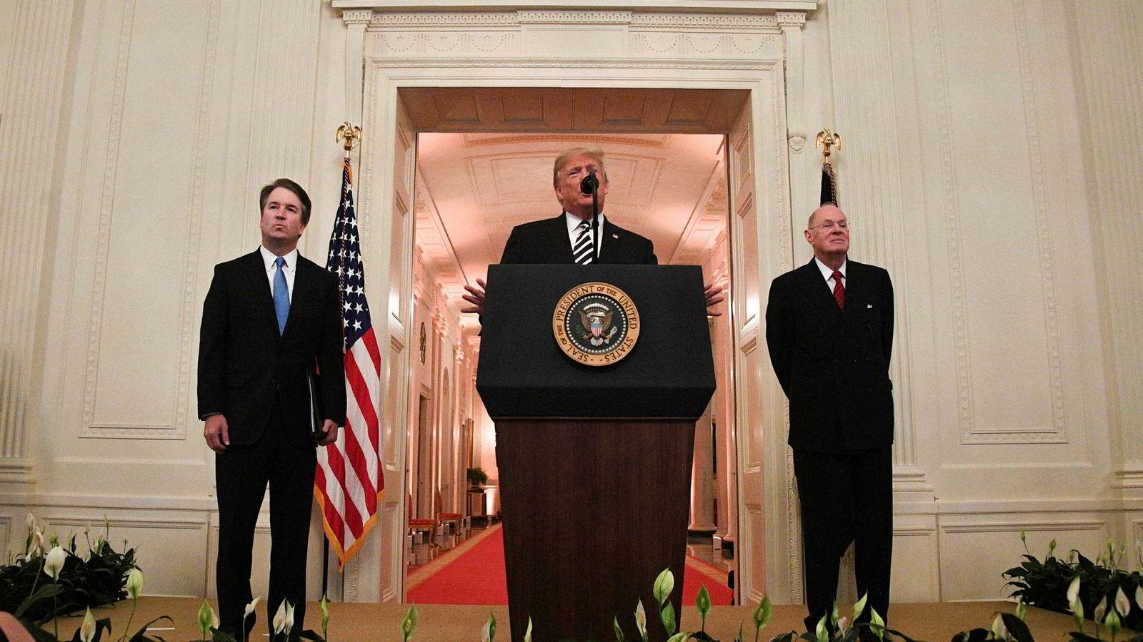 Brett Kavanaugh (til venstre) og pensjonert høyesterettsdommer Anthony Kennedy (til høyre) hører på Donald Trumps tale under seremonien i Det hvite hus mandag.