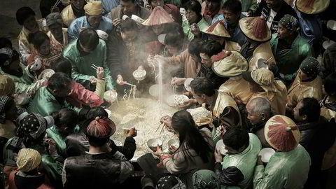 Kinesere, iført drakter fra Qing dynastiet, feirer guden Nuwa med et stort festmåltid bestående av nudler. Bildet er fotografert av den kinesiske fotografen Jianhui Liao og er kåret til årets matfoto av konkurransen The Foodphotographer of the year.