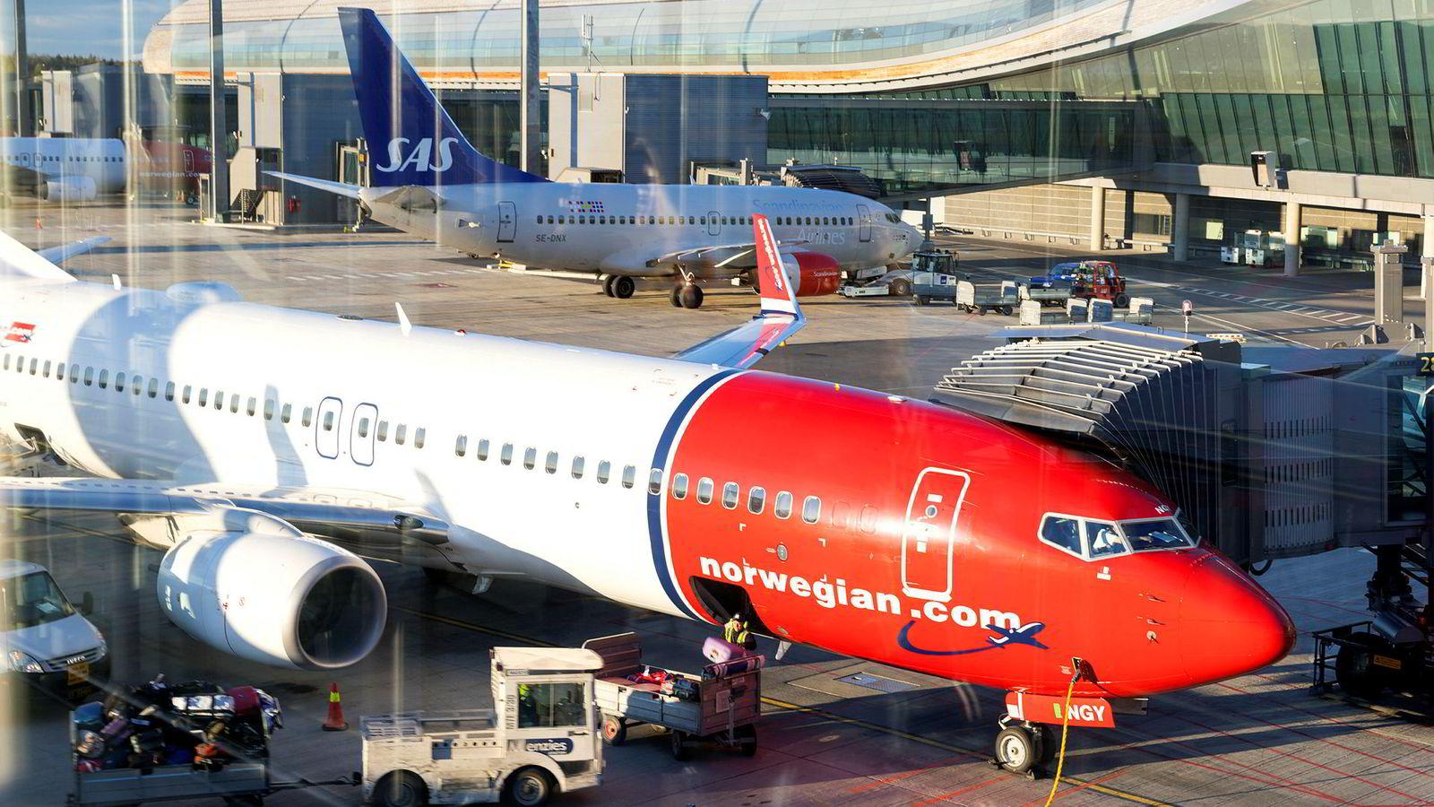 Avinor har inngått en samarbeidsavtale om produksjon av biodrivstoff basert på norsk biomasse med selskapet Quantafuel. Her er et Norwegian- og et SAS-fly på Gardermoen.