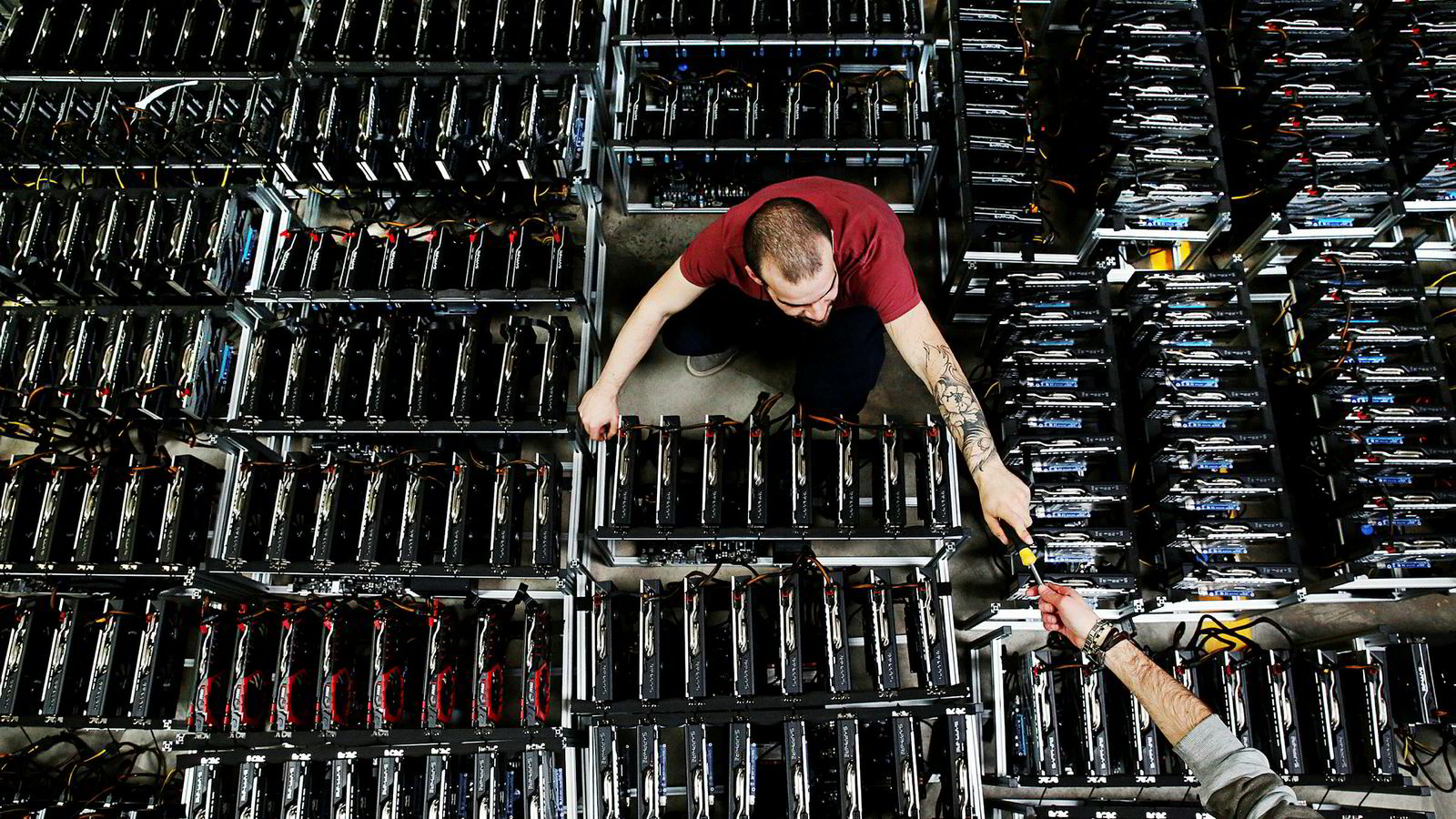 Ansatte jobber med en maskin som brukes til å utvinne bitcoin ved Bitminer Factory i Firenze.