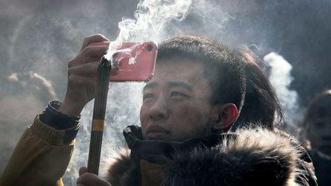 Børsverdier på 400 milliarder dollar har forsvunnet for Apple siden oktober. Her tar en kinesisk mann bilder med en Iphone under nyttårsfeiringen.
