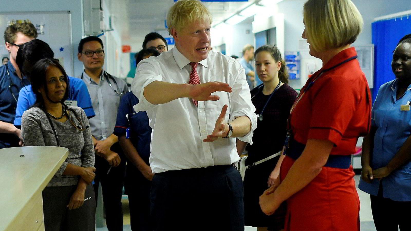 Britenes statsminister Boris Johnson tar av hanskene. Her under et besøk på et sykehus i Watford utenfor London denne uken.