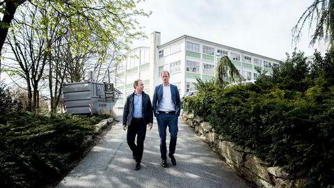 Daglig leder i K2 Bolig Sigve Hebnes (til venstre) og Øyvind Mikalsen i Camar Eiendom på tomten de har kjøpt i Stavanger sentrum. Den store lagerhallen i bakgrunnen er vernet og skal beholdes. Foto: Tommy Ellingsen