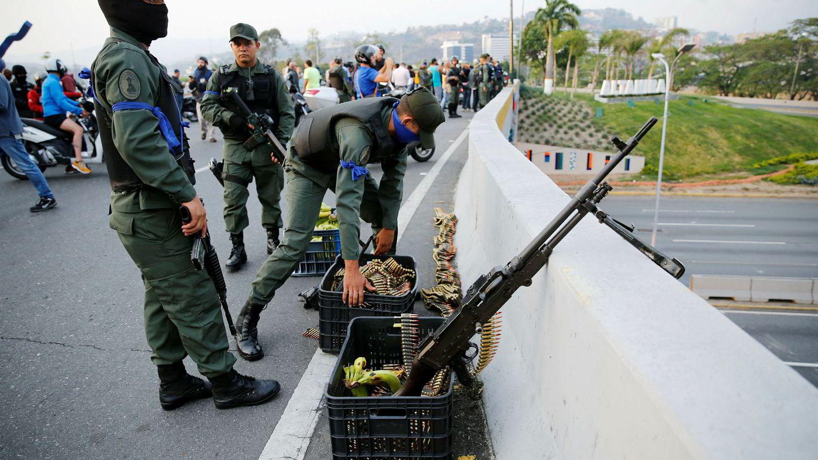 Soldater som har meldt overgang til opposisjonen forsvarer luftbasen Carlota ved hovedstaden Caracas.