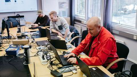Hydro-ansatt Ole Morten Lie (til høyre) jobber vanligvis med maskinvedlikehold, men har jobbet mer enn fulltid med it-arbeid etter hackerangrepet. – Jeg har gått ut av telling. Måtte begynne å bruke melk, sier han om de siste ukenes kaffeforbruk på møterommet som er blitt «krigsrom» for pc-rensing etter hackerangrepet. Fra venstre it-supportmedarbeiderne Axel Palmcrantz, som har fløyet mellom europeiske fabrikker etter angrepet, og Andreas Haugsvær, som vanligvis jobber på Hydros hovedkontor på Vækerø.
