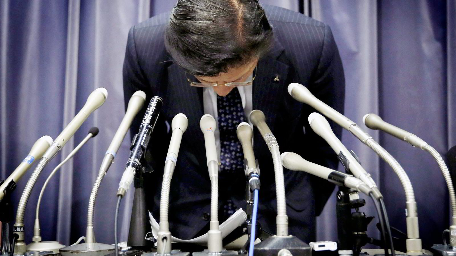 Konsernsjef Tetsuro Aikawa i Mitsubishi Motors bukket dypt foran kameraene på pressekonferansen onsdag før han bekreftet ryktene som begynte å gå i japanske medier tidligere på dagen. Foto: Toru Hanai/Reuters/NTB Scanpix