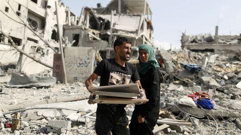 UBEBOELIG: En palestinsk mann bærer eiendelene sine etter å ha kommet tilbake til sitt ødelagte hus i Beit Hanoun. Foto: