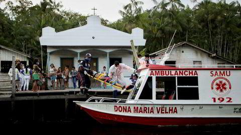 Maria Angela (56) bæres om bord i en ambulansebåt fra sitt hjem i elvesamfunnet Menino de Deus, dypt inne i Amazonas. Det er mange timer i båt til nærmeste sykehus.