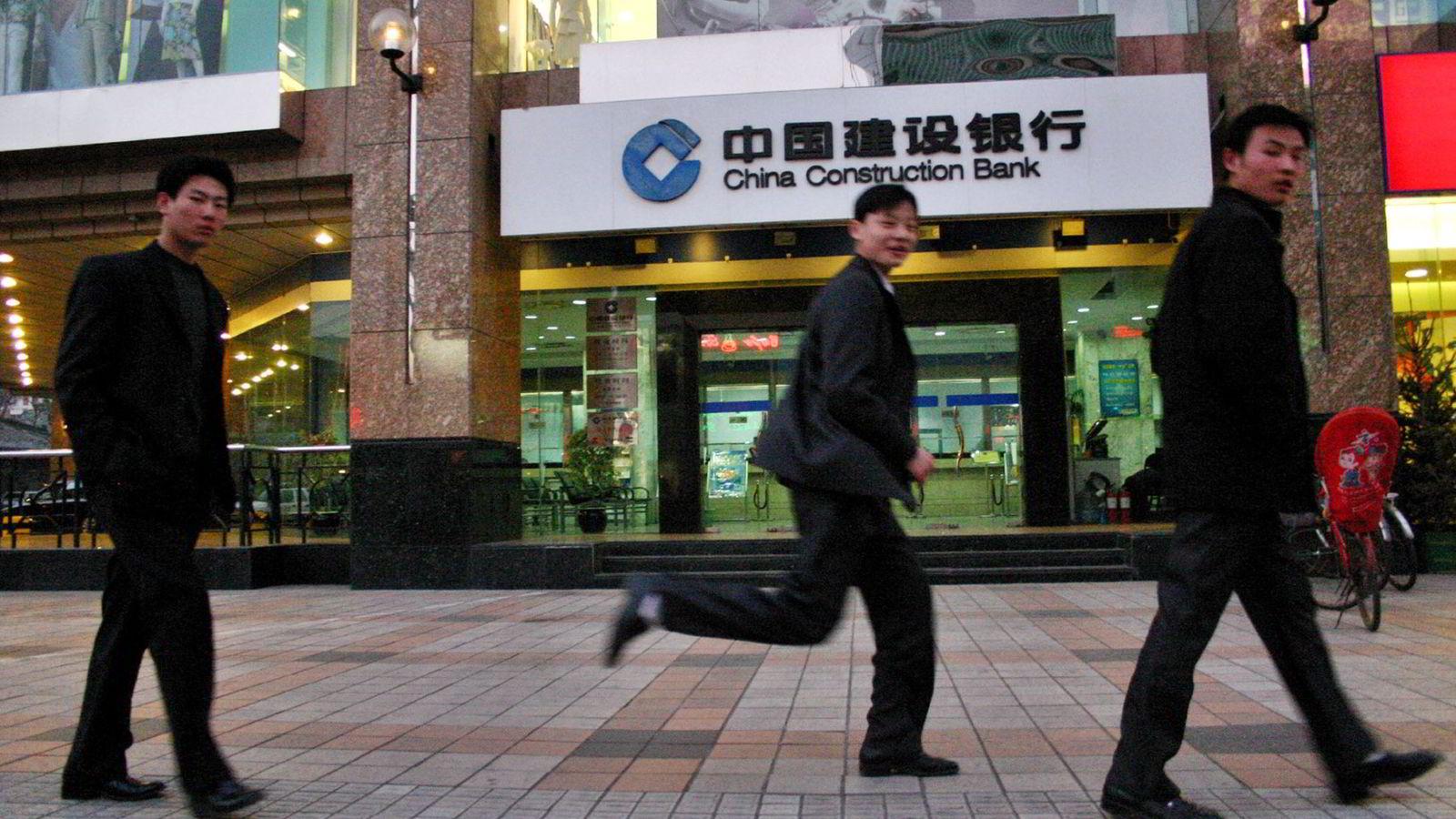 Myndighetene i Kina har så langt vært raske til å tilføre bankene frisk kapital ved det minste tegn på spredning til økonomien i landet. På bildet passerer fotgjengere en filial til China Construction Bank. Foto: AP Photo/NTB scanpix