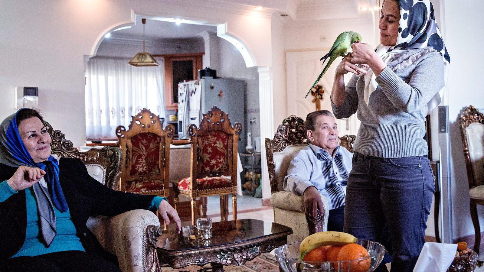 Kreftsyke Abolghasem Eskandari (midten) finner trøst i bestevennen, papegøyen Messi. Hver gang han går ut av døren roper papegøyen «bye». Til høyre står datteren Parvaneh Eskandari som mistet ektemannen for syv år siden, mens moren Khadijeh Daneshmayeh sier hun merker hvordan sanksjonene påvirker hele familien. Foto: Aleksander Nordahl