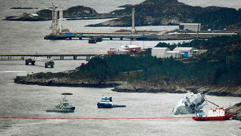 """Den norske fregatten """"KNM Helge Ingstad"""" ligger med slagside nær land etter at den kolliderte med tankskipet """"Sola TS"""" natt til torsdag. Deler av Stureterminalen i bakgrunnen."""