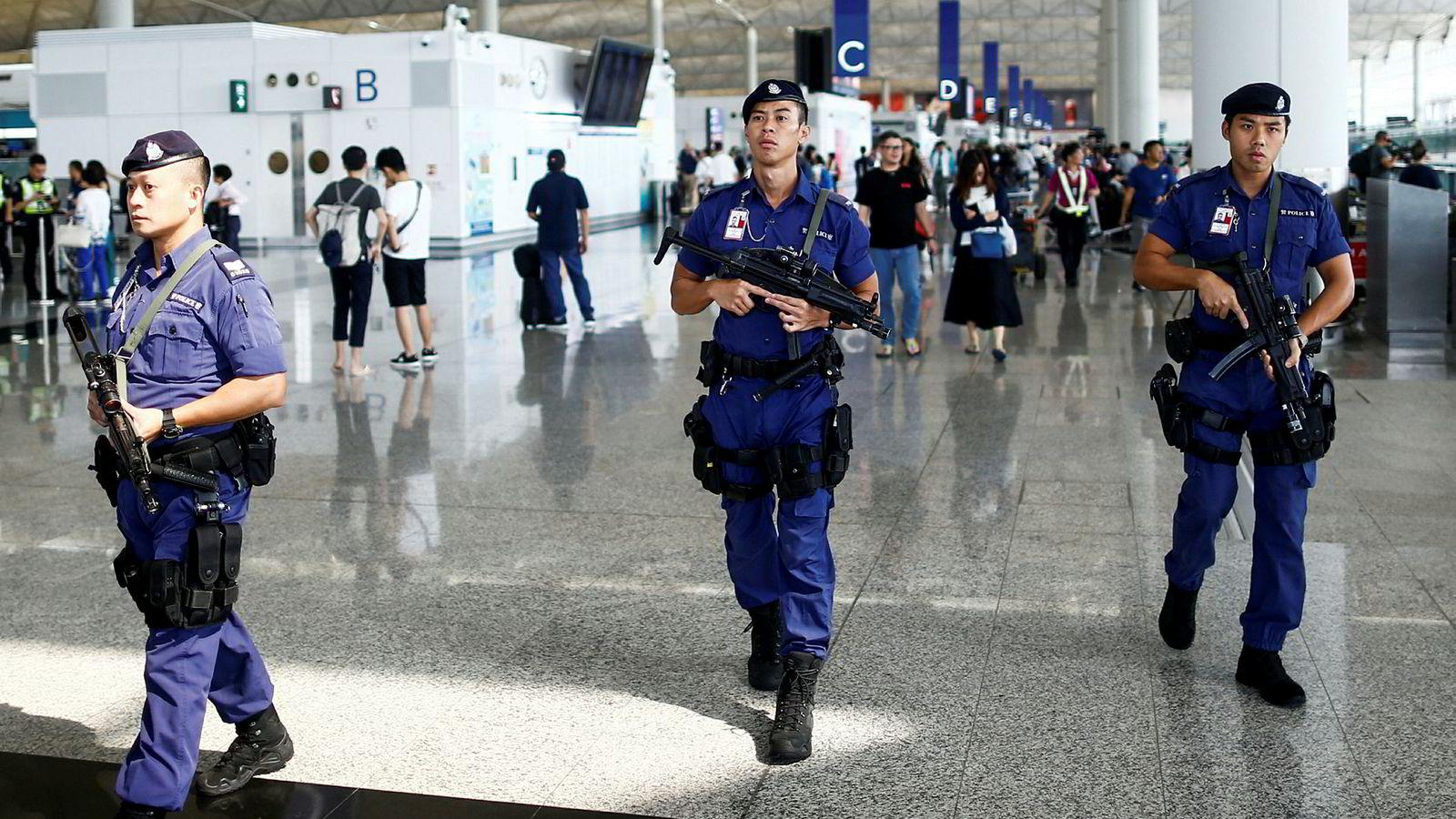 Bevæpnet politi patruljerer nå på flyplassen i Hongkong.