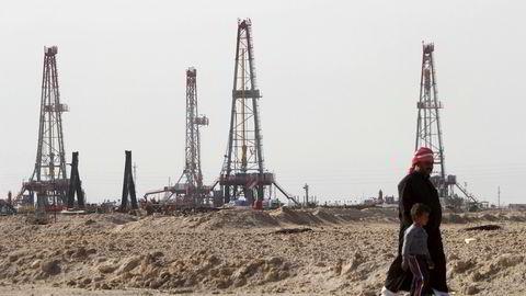 To personer går forbi oljefeltet Basra i Irak. Illustrasjonsfoto: REUTERS/Essam Al-Sudani