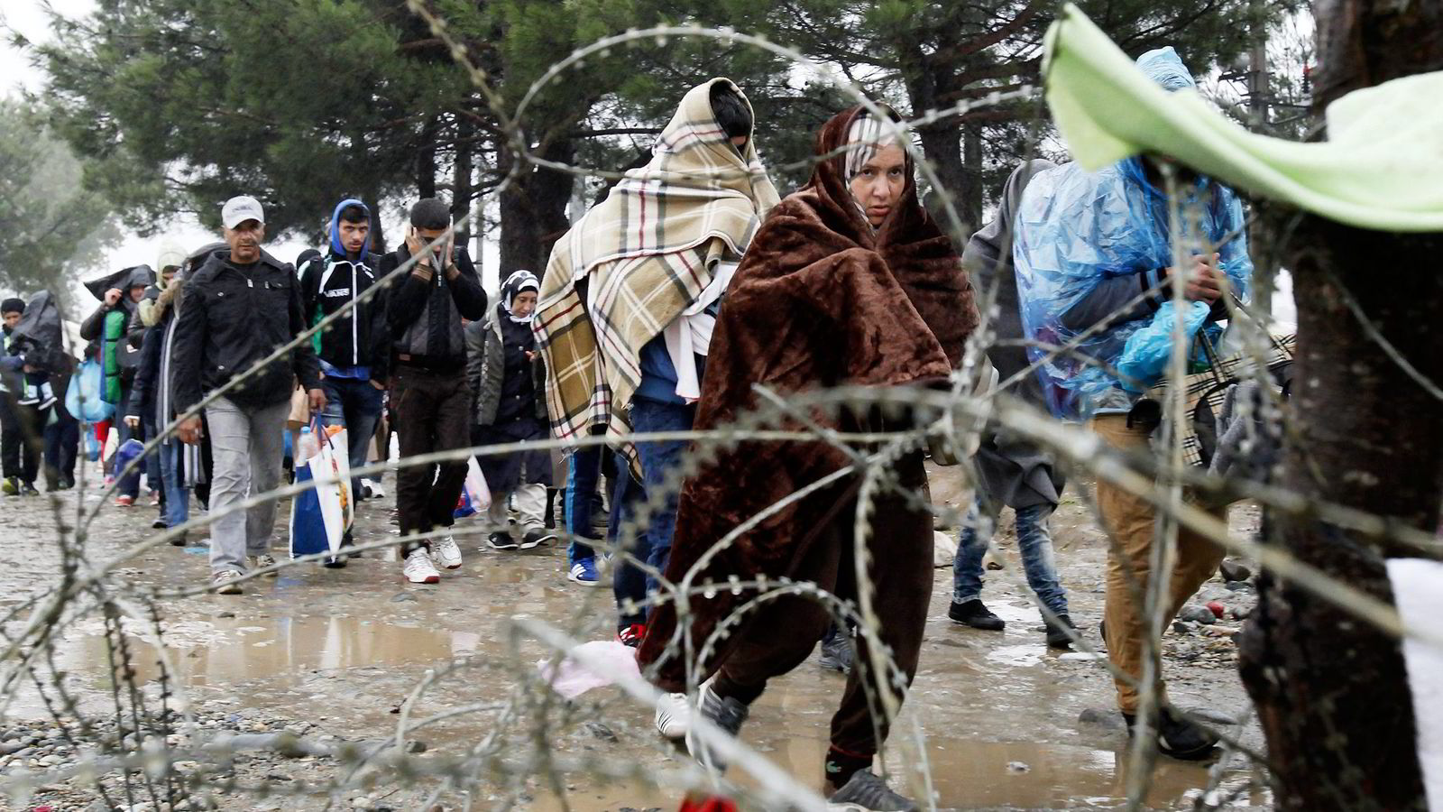 Europakommisjonen frykter at den kommende vinteren kan gi stygge scener med flyktninger i nød. Her krysser flyktninger grensen mellom Hellas og Makedonia. Foto: Boris Grdanoski, AP/NTB Scanpix