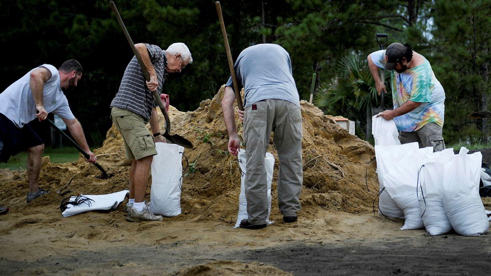 Orkanen Michael nærmer seg kysten av Florida. På bildet forbereder folk seg med å fylle i sandsekker tirsdag.