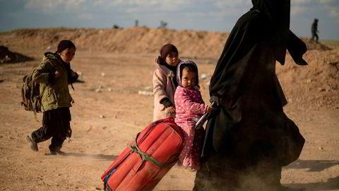 En kvinne og hennes barn flykter i mars ut Baghouz i mars som var det siste området terrororganisasjonen IS kontrollerte. Nå strever Norge og andre land med å finne ut i hvilken grad og hvordan de skal hjelpe barn av IS-medlemmer ut av flyktningleirer i Syria.