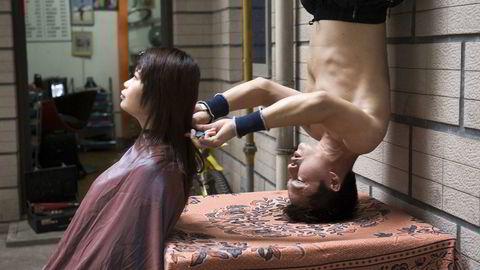 Her klipper Wang Xiaoyu (35) håret til en kunde i sin frisørsalong i Changsha, Kina mens han står på hodet. Veksten i Kinas tjenesteytende sektor er den laveste på halvannet år, viser ferske tall. Arkivfoto: