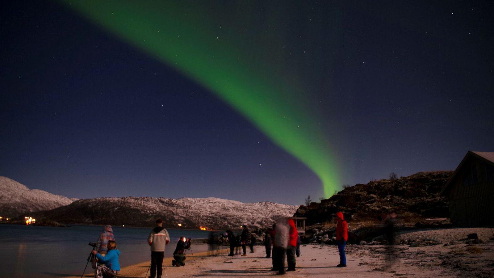Et titall turister fotograferer og opplever nordlys på stranden til Tromsø Friluftssenter i Risvika på Kvaløya utenfor Tromsø.