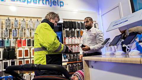 – Bestefar jobbet lenge i Televerket. Så jeg har et nært forhold til Telenor, sierArve Berggren Teigseie som benytter swap for å kjøp av ny telefon. Her sammen med datteren Renate og hennes mor Reannie ytterst til høyre. Butikksjef Umar Hussain til høyre i Telenor-butikken i Oslo City registrerer økt mobilsalg etter swap-lanseringen.