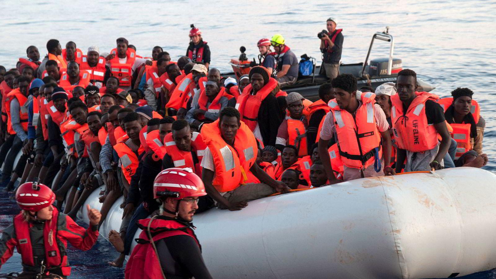 Migranter i en gummibåt blir ført over i et redningsskip i Middelhavet tidligere denne måneden.