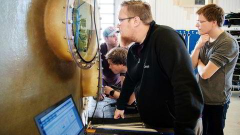 Bjørn Folkvord Esaiassen ser inn i en vanntank under test av en undervannsrobot hos Icsys på Klepp. Bak fra venstre Thomas Aunvik, Sven Hatteland og Vidar Haus.