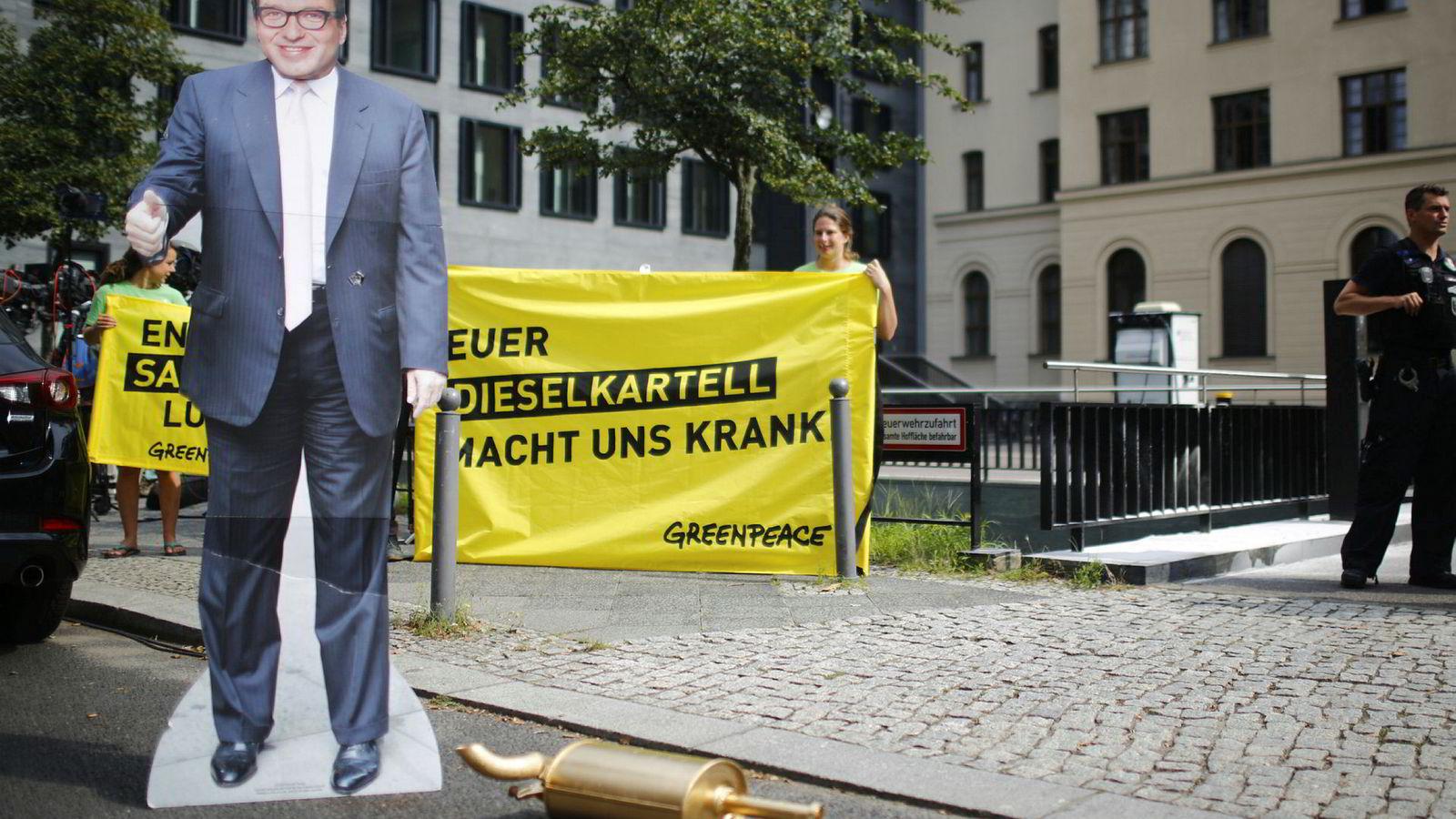 Demonstranter utenfor Tysklands føderale departement for transport og digital infrastruktur med en plakat av transportminister Alexander Dobrindt - som i dag møter Tysklands omstridte bilindustri.