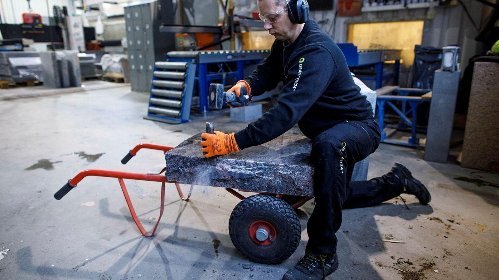 Steinarbeider Marek Kusztal hakker for hånd røffe kanter på polert larvikitt.
