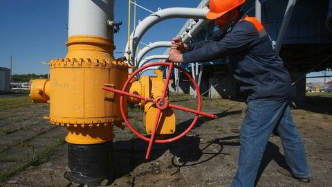En ansatt skrur på gassrørledningen i Lvviv-regionen i Ukraina. Store deler av den russiske gassen til Europa går via rørledningen som passerer gjennom Ukraina.