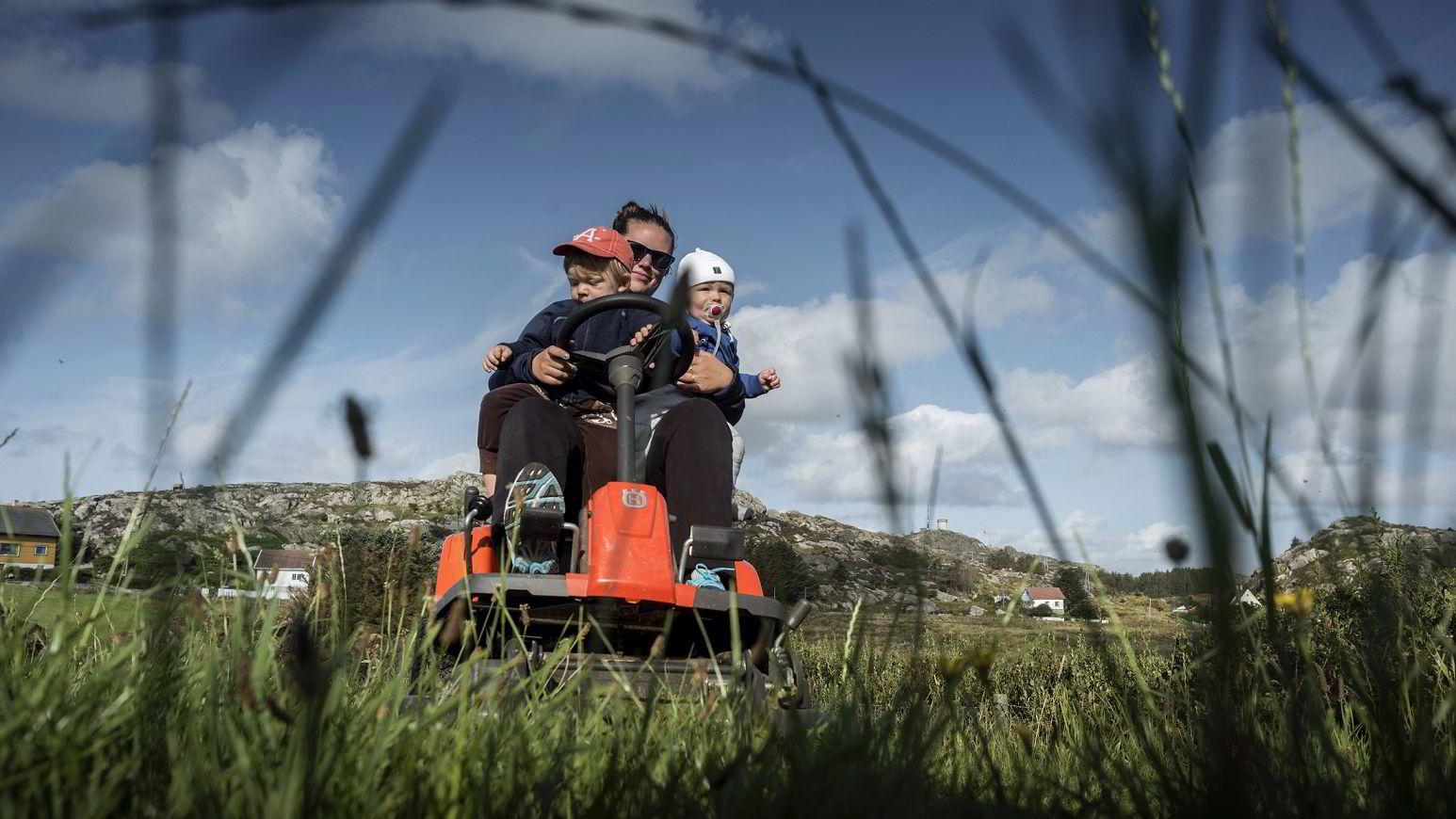 Katrine Klovning holder gresset nede på familiegården på Utsira mens sønnene Victor (2) og Henrik (1) følger med på hvert sitt kne.
