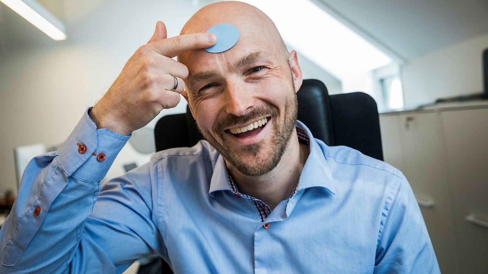 Gründer og daglig leder Kjetil Meisal i Onio viser hvordan sensorer kan festes i pannen eller andre egnede steder, for å måle feberutviklingen konstant.