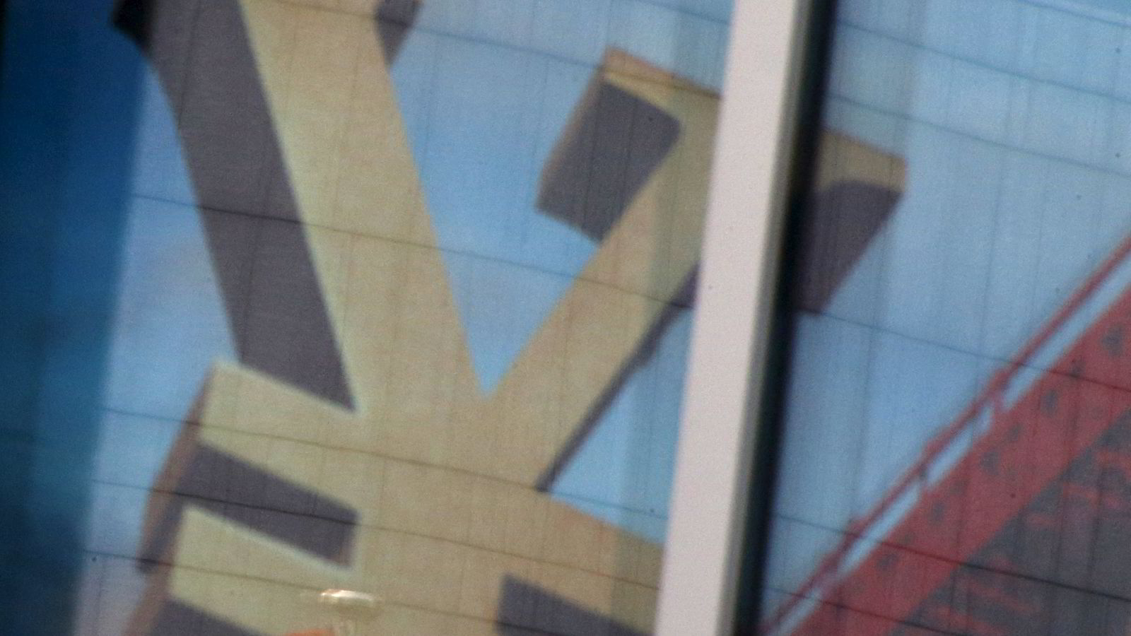 Tegnet for Kinas valuta reflekteres i vinduet i en bankbygning i Kina. Foto: Kim Kyung-Hoon/Reuters/NTB SCANPIX