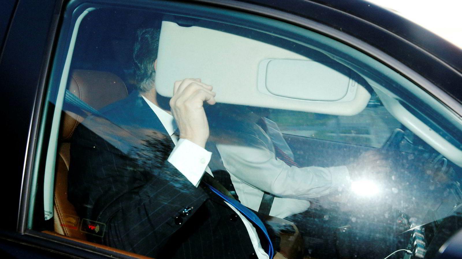 Donald Trumps tidligere kampanjesjef, Paul Manafort, gjemmer seg bak solskjermen i det han forlater hjemmet sitt i Virginia.
