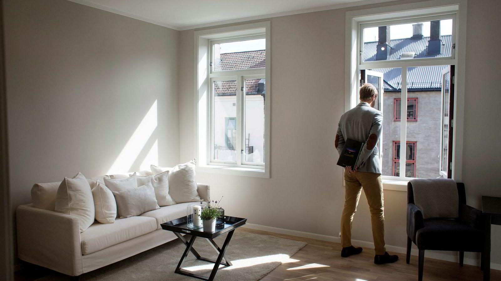 En eiendomsmegler venter på besøkende til en leilighetsvisning. I storbyene er det blitt nesten umulig for unge uten formue å kjøpe leilighet,