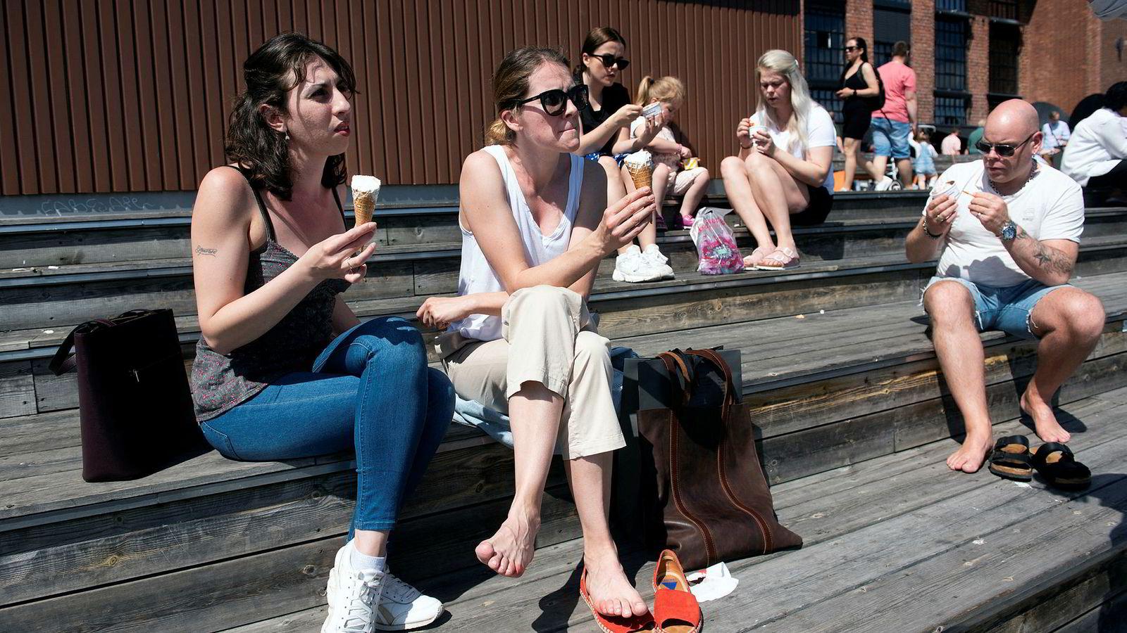 Sommer og is på Aker Brygge. Venninnene Dajana Draskovic (til venstre) og Oksana Bukhney nøt sommeren på bryggekanten. I bakgrunnen Ida, Mari, Renate og Endre Lindström ferierende fra Sogndal.