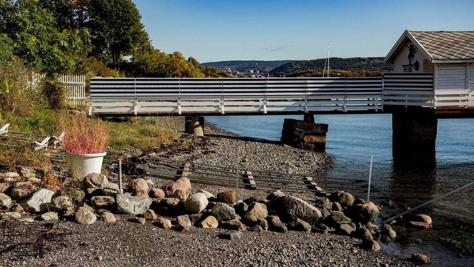 Milliardær Christian Ringnes har fjernet plankekrysset som var oppført under gangbroen ut til badehuset. I forgrunnen ligger vannscooterslippen og steinskillet som kommunen også har vurdert.