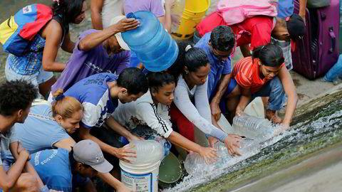 Folk forsøker desperat å samle opp vann fra en lekk vannledning ved elven Guaire i Venezuelas hovedstad Caracas.