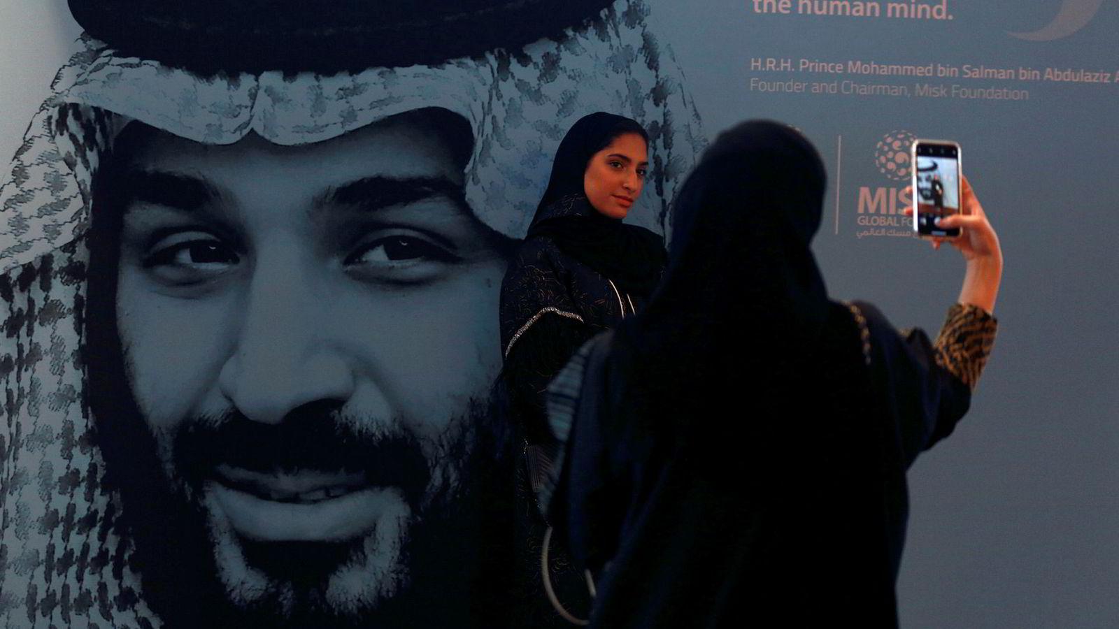 Saudi-Arabia mener USA driver med «innblanding» om konflikten i Jemen. Kvinnene på bildet fotograferer hverandre foran et stort bilde av kronprins Mohammed bin Salman.