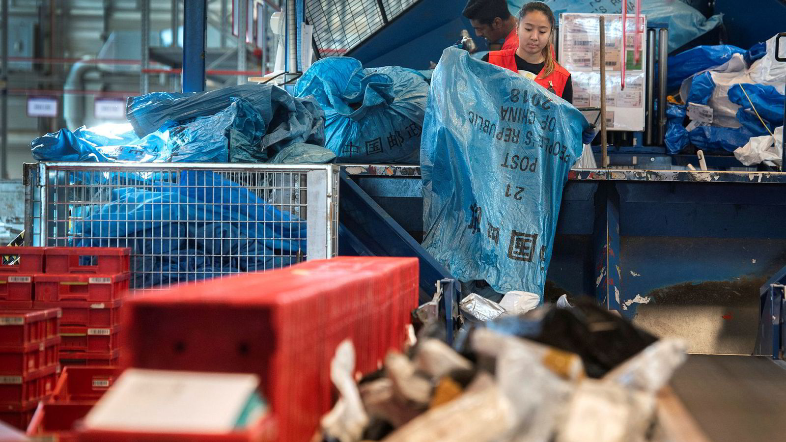Annie Nguyen tømmer store sekker med post fra Kina ved postens Østlandsterminal på Lørenskog. I bakgrunnen Deefar Santhanam.