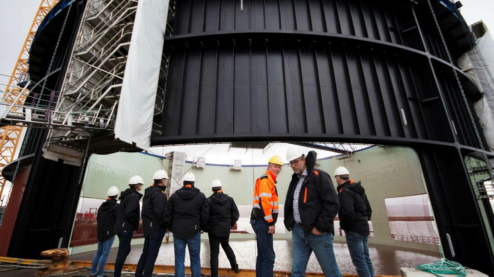 En delegasjon fra Norsk Fisketransport og Midtnorsk Havbruk ser på bygging av sin nye stålmerd på Fosen Yard ved Trondheimsfjorden. I oransje kjeledress administrerende direktør Anders Straumsheim i Fosen Yard, foran til høyre prosjektleder Steingrim Holm.