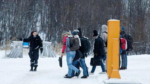 En politikvinne viser en gruppe asylsøkere videre på Storskog grenstasjon i Finmark. Foto: Cornelius Poppe,