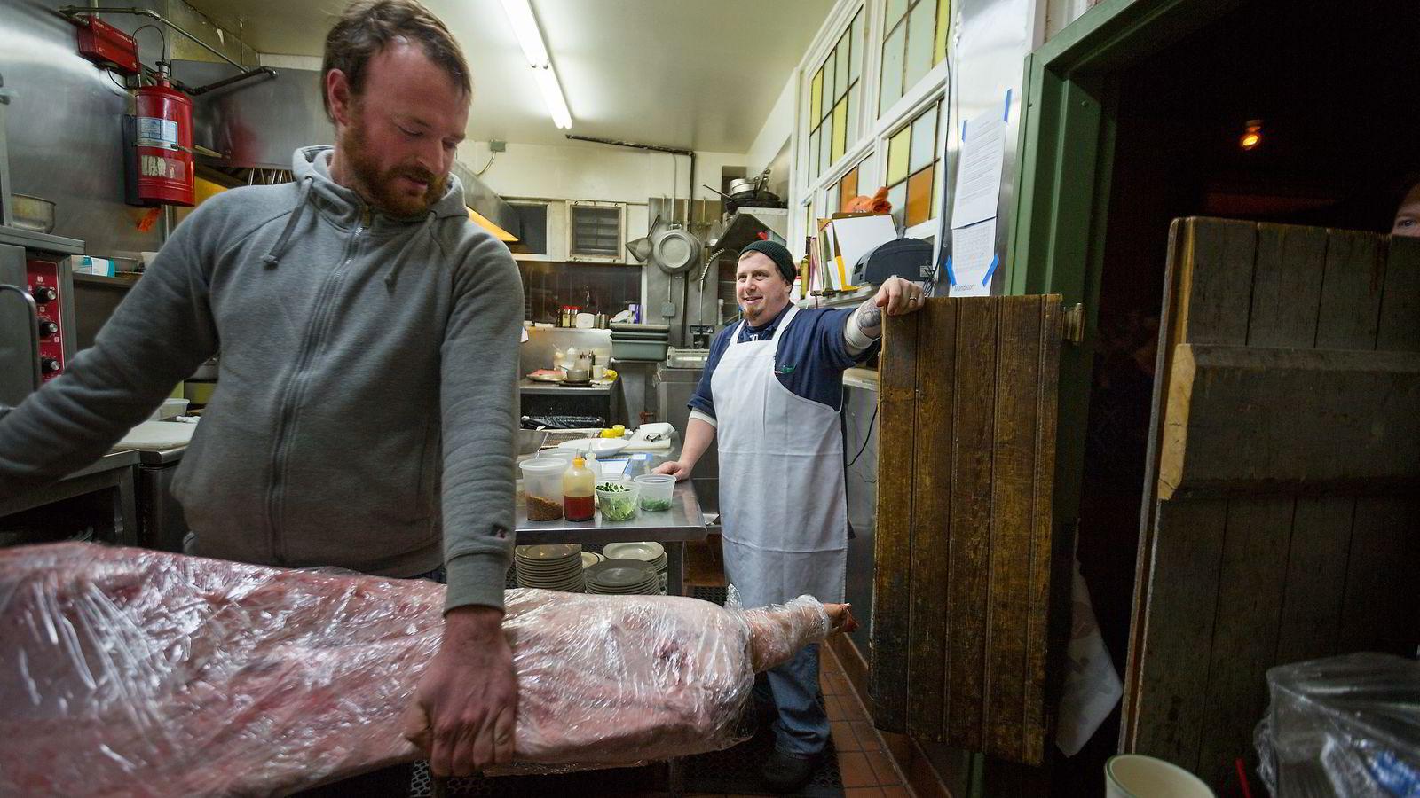 Kokk Kevin Adey inspiserer den halve grisen han har fått levert fra bonde Nick Westervelt (til venstre) .