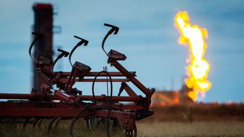 Flammene fra faklingen av en brønn skyter opp i bakgrunnen på et jorde der det drives skiferoljeutvinning, USA. Foto: