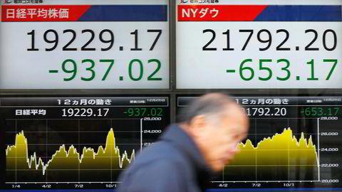 En mann passerer skjermer som viser fallet på den japanske børsen i Tokyo første juledag.
