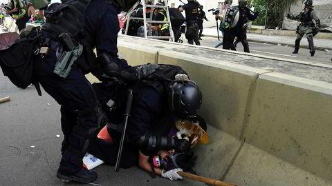 En mann blir lagt i bakken av politiet under demonstrasjonene i Hongkong lørdag.