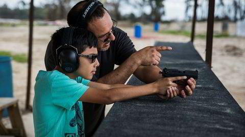Elizar Flores lærer opp sønnen på ti år til å bruke et håndvåpen med magasin på en skytebane i Houston. Texas er én av statene der våpenlover kan bli avgjørende tema i høstens mellomvalg i USA.