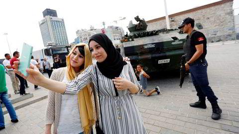 Det mislykkede militærkuppet har gjort Tyrkia-ferien enda billigere for turistene. Her tar to turister fra Algerie bilde foran en forlatt tanks. Foto: Murad Sezer/Reuters/NTB Scanpix