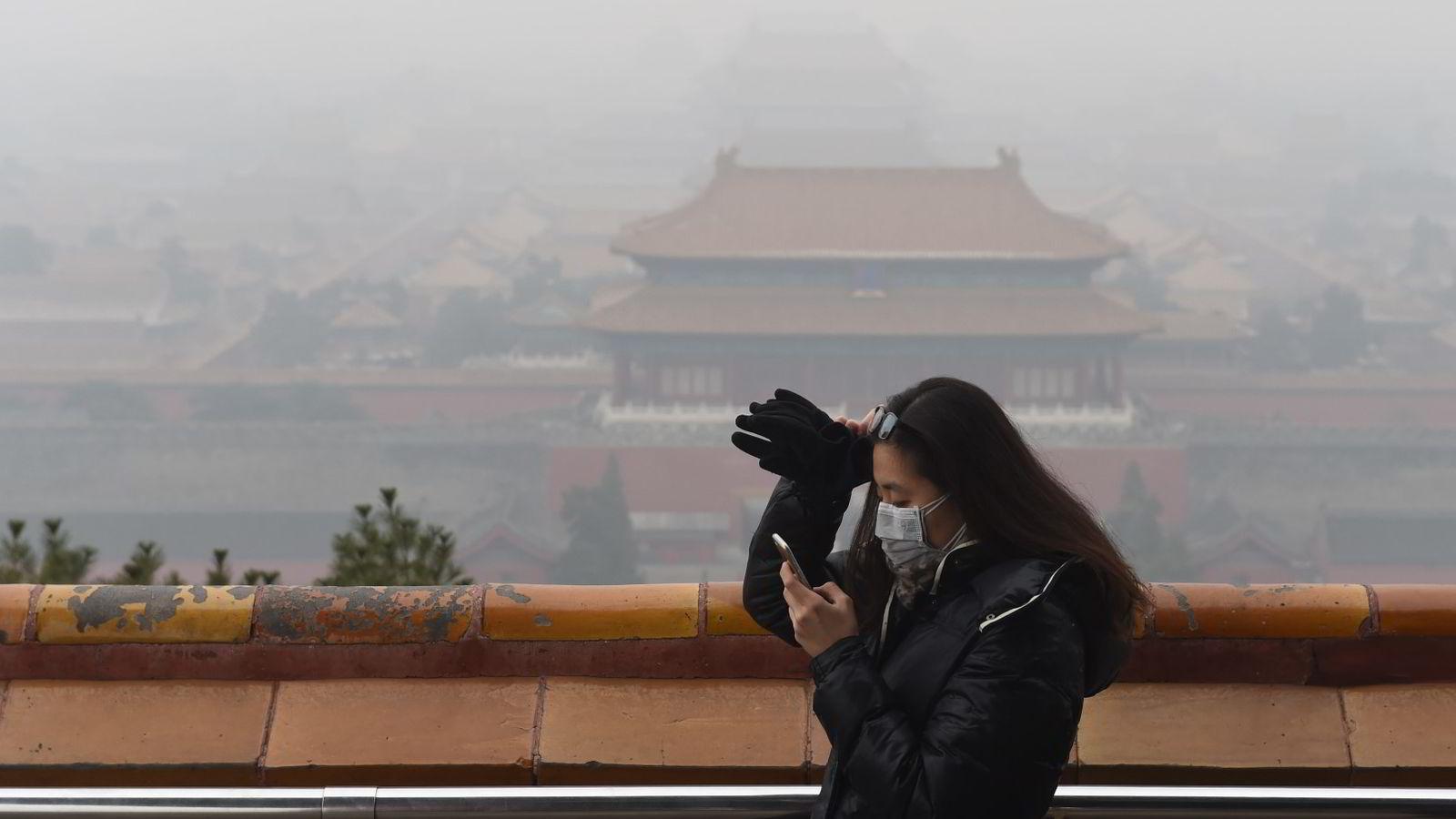 Luftforurensningen i Beijing og andre kinesiske byer er verre enn noensinne. På bildet sjekker en kvinne sin smarttelefon foran Den forbudte by i Beijing. Foto: Greg Baker/AFP photo/NTB scanpix