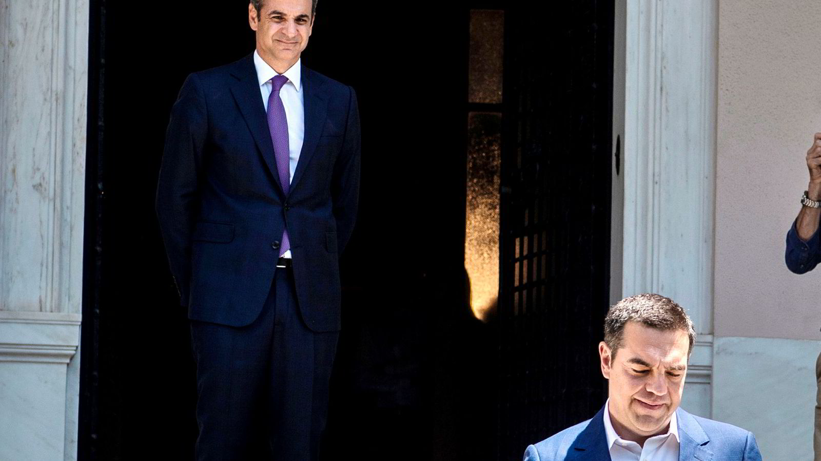 Greece's new conservative Prime Minister Kyriakos Mitsotakis (L) watches his predecessor Alexis Tsipras leaving the Maximos Mansion after their meeting, after being sworn-in on July 8, 2019 following a sweeping election victory put him in charge of the EU's most indebted member with promises to end a decade of economic crisis. - The 51-year-old Harvard graduate and former McKinsey consultant took the oath of office in the presidential mansion in the presence of his wife and three children. (Photo by ANGELOS TZORTZINIS / AFP) ---